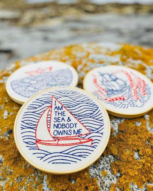 Embroidery hoop on a rock that says 'I am the sea & nobody owns me'