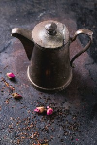 Vintage teapot with dry tea and rose buds over black metal background