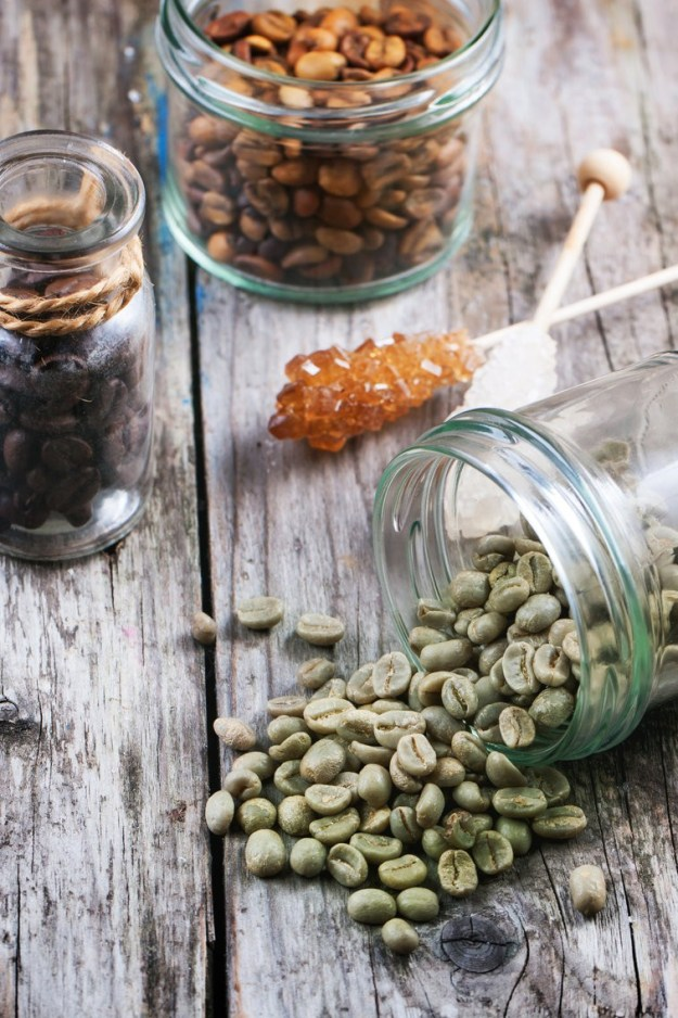 Green, brown unroasted decaf and black coffee beans in glass jars over wooden background. See series