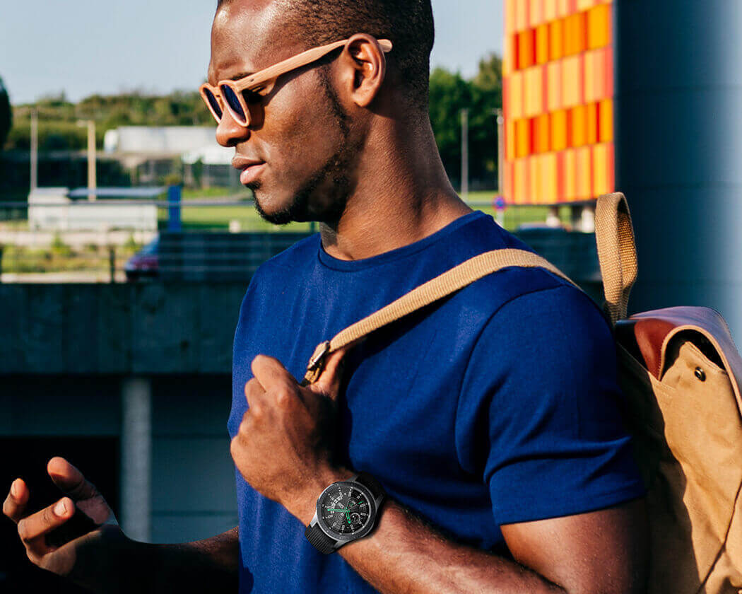 Left side of a man outside in a blue t-shirt, yellow glasses and yellow backpack, wearing a Silver 46mm Galaxy Watch.