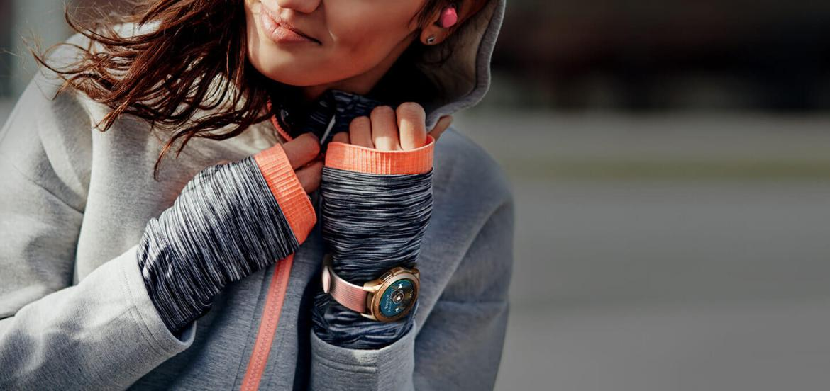 A woman in grey and orange jogging gear on a run wearing a 42mm Rose Gold  Galaxy Watch and pink Icon X earbuds.