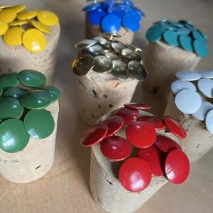 vintage metal tacks organized and displayed by color on vintage cork bottle stoppers