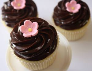 A pretty Sakura cherry blossom atop chocolate frosted cupcakes