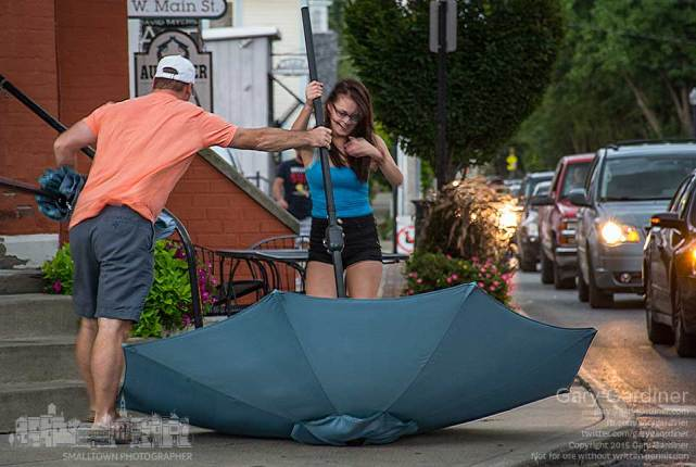A passerby helps one of the baristas at Heavenly Cup retrieve one of the coffee shopÕs umbrellas before it blows into the street during a rain storm Uptown.