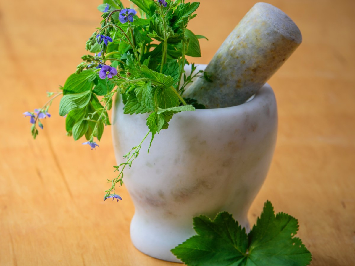 A mortar and pestle containg herbs to symbolize the natural ingredients in healthful deodorants