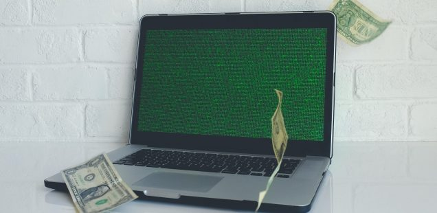 image of a laptop computer with dollar bills falling around it, symbolizing profit from technology. Photo by NeONBRAND on Unsplash.