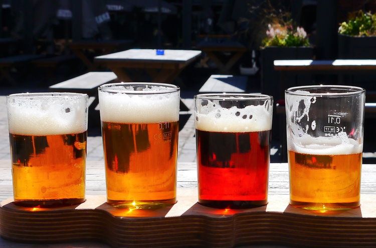 Row of beers in small glasses outside