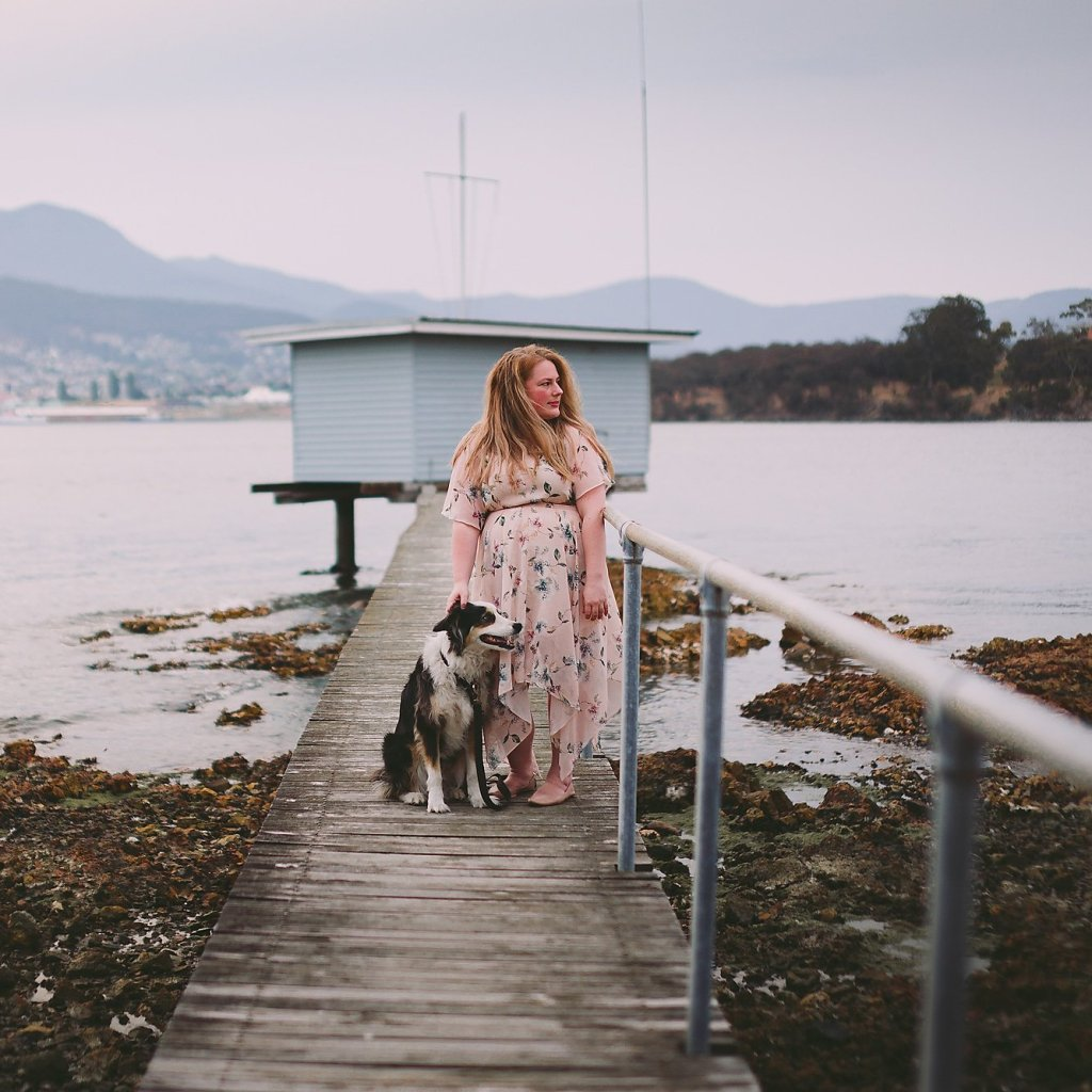Picture of water in background.  Australian Shepherd and Girl standing on a wharf looking out off screen