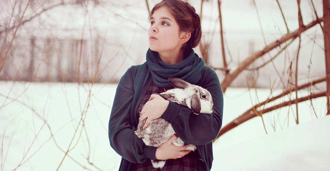 girl with heidi braid in the winter by the river with a rabbit in her hands