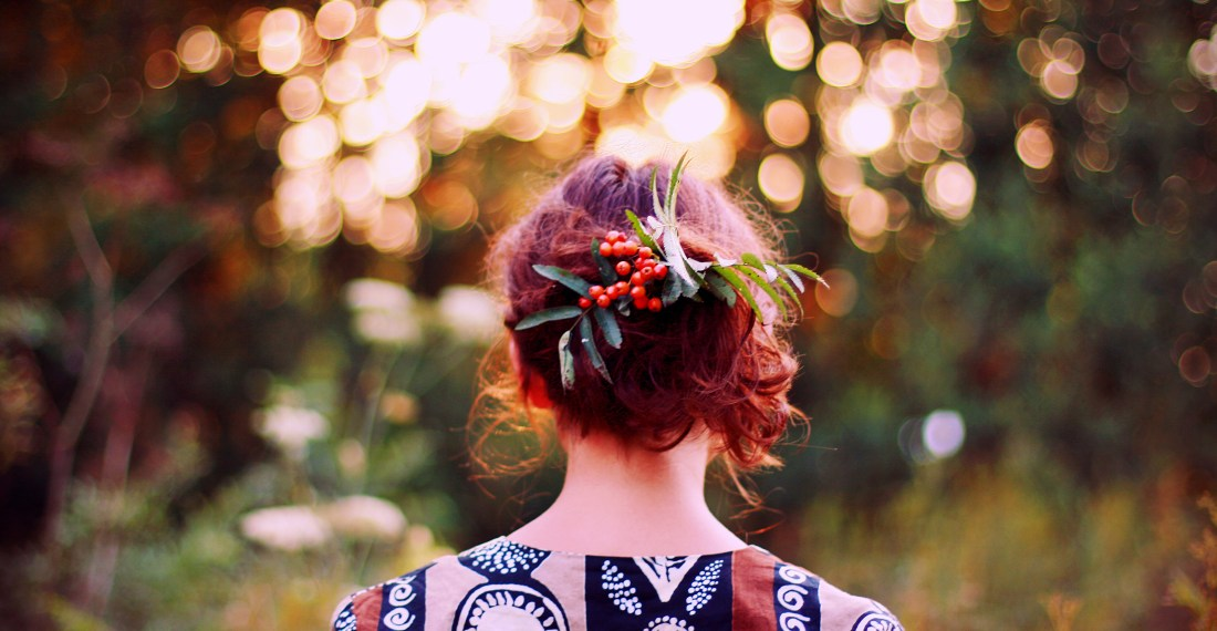 girl with rowans in her hair in front of a forest in sunset