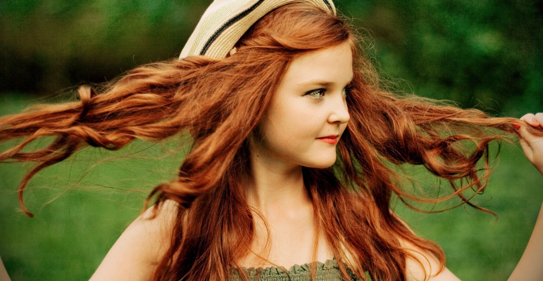 cute redhead girl with a hat pulling her hair