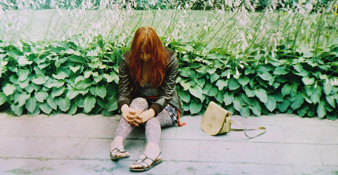 film analogue image of a girl sitting on the pavement beside some greenery with her bag on her side