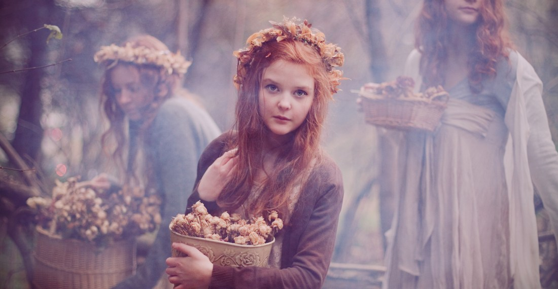 three redhead girls with flower crowns in a fog smoke in the forest with baskets of dry flowers