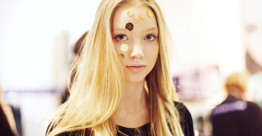 fashion week backstage portrait of a cute baby face blond Lithuanian model with gold stickers on