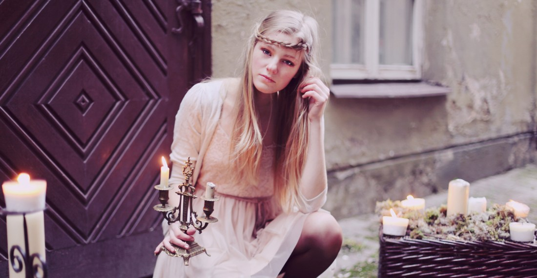 blond girl with braid in her hair is crouching holding a candle with many other candles around her