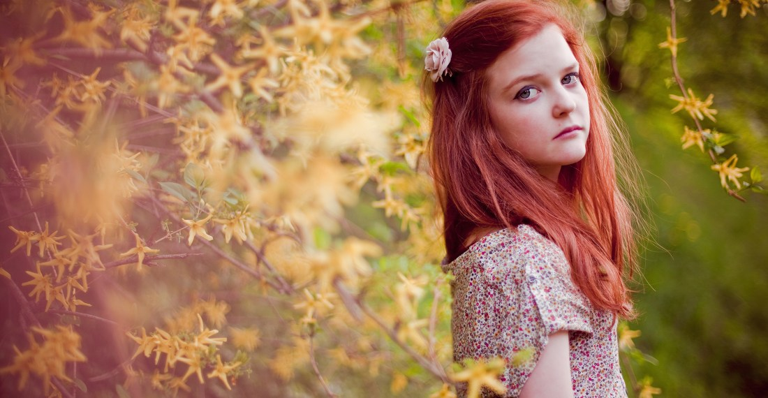 redhead girl in front of dreamy yellow flower bush