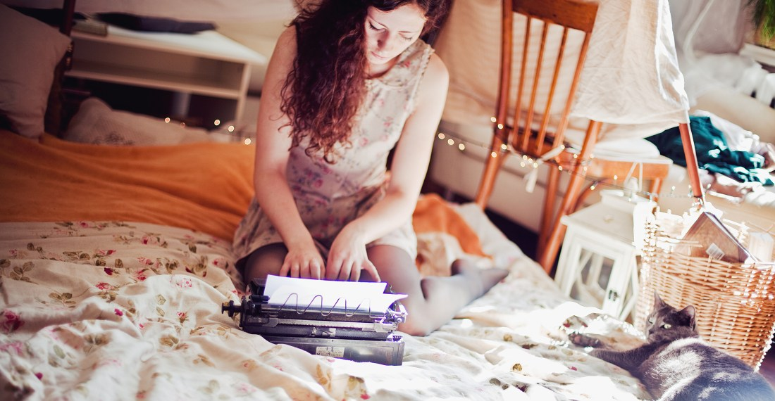 girl with dark curly hair in the tent in a room with a cat and a typewritter