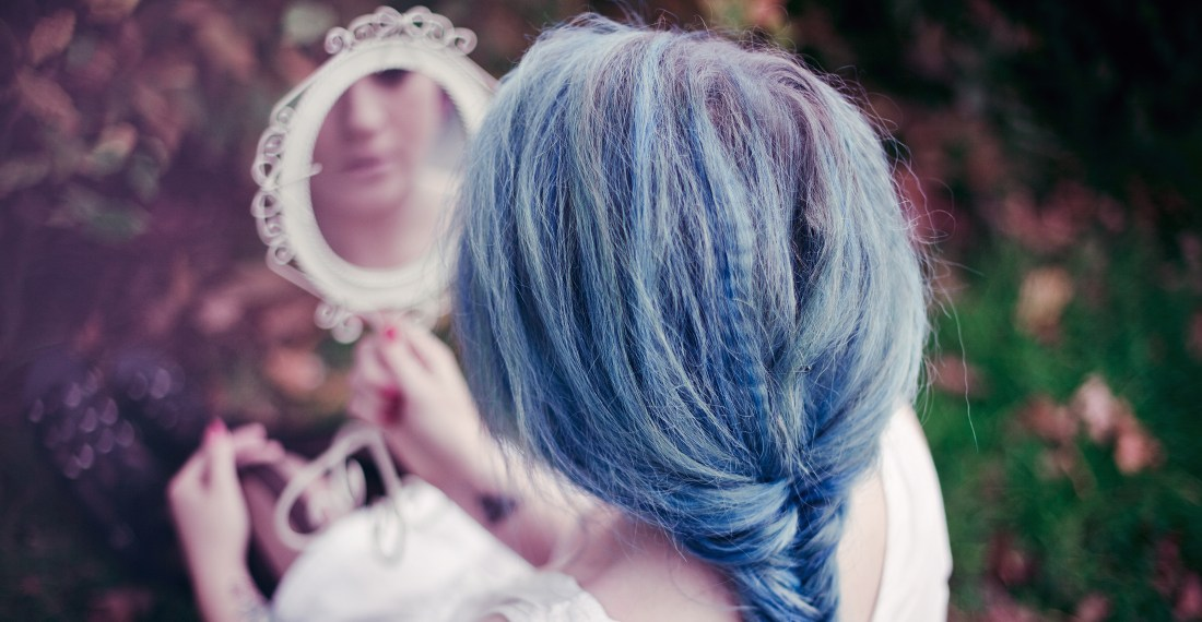 girl with blue hair in a braid sitting in autumnal park with a white vintage mirror