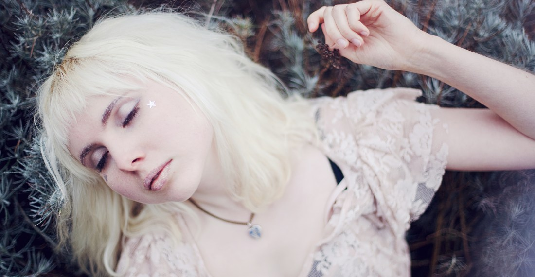girl with blond hair and a fringe in a lace dress lying in a park with eyes closed