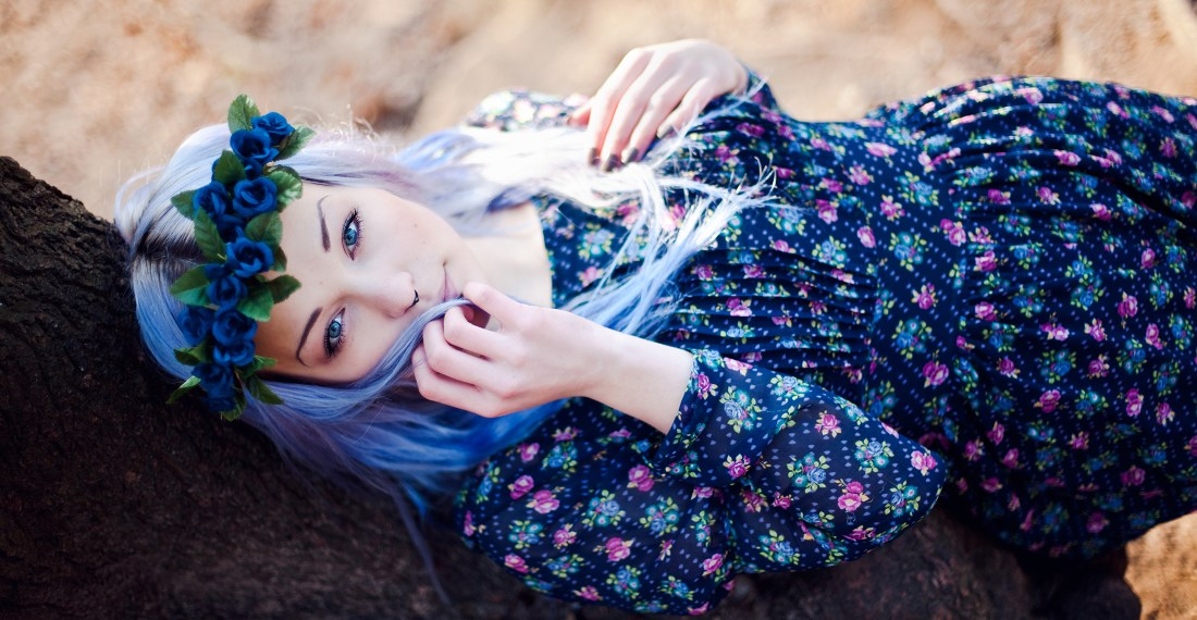 girl with blue hair and a flower crown in a forest