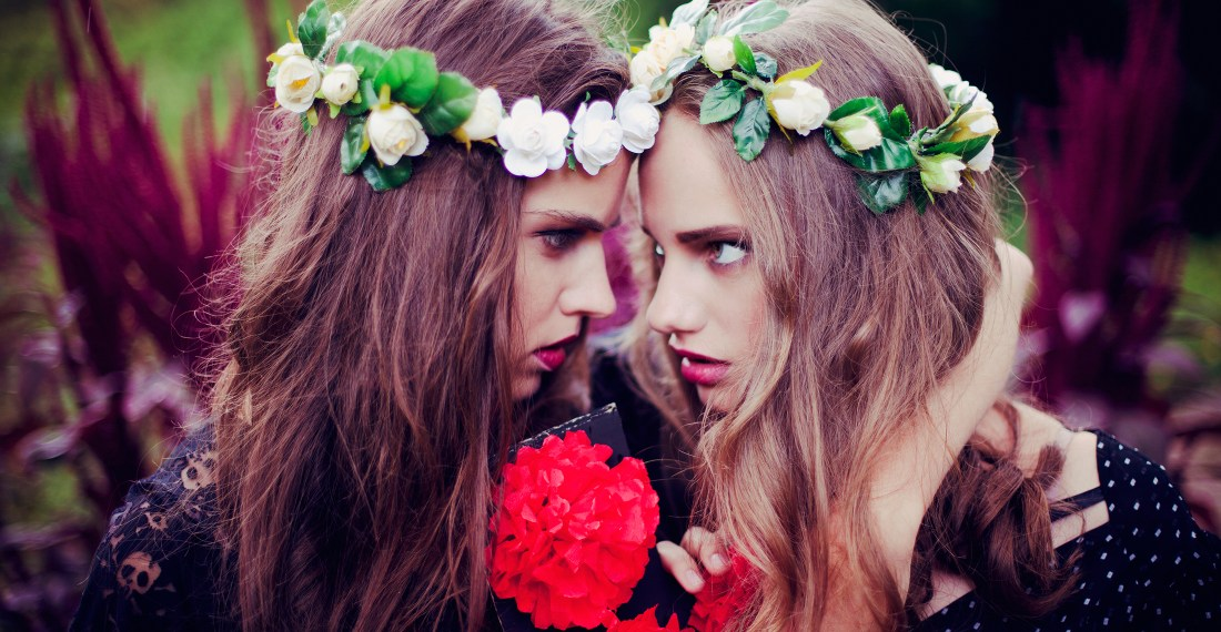 girls with flower crowns on in a garden look intensely at each other
