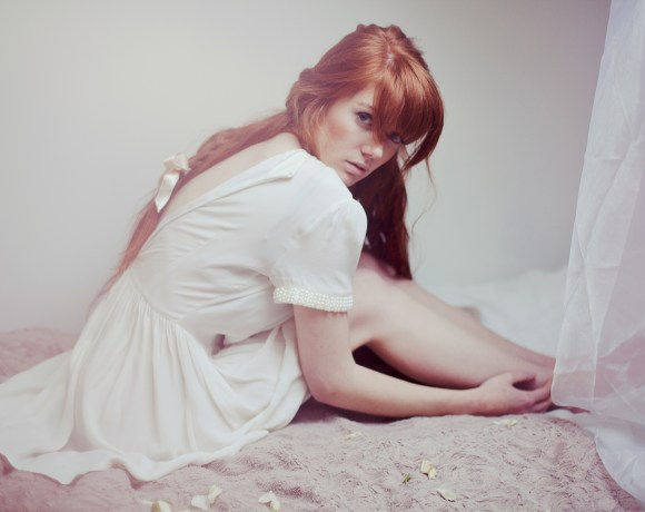 emotive portrait of a girl with red hair in a braid in white dress sitting on a bed