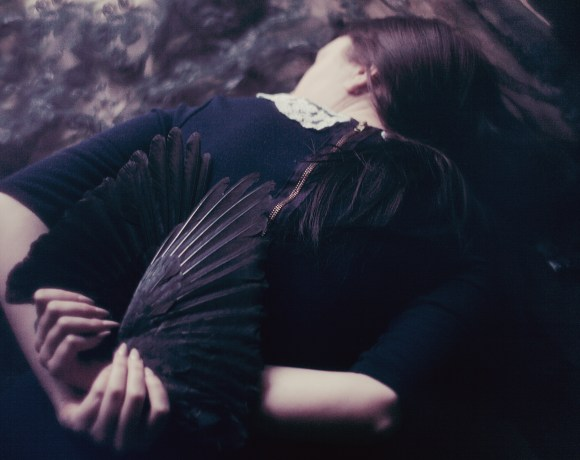 dark emotive picture of a girl lying on her back with raven wings