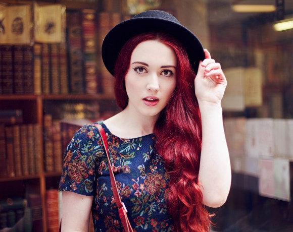 redhead blogger with a hat on in front of a bookshop