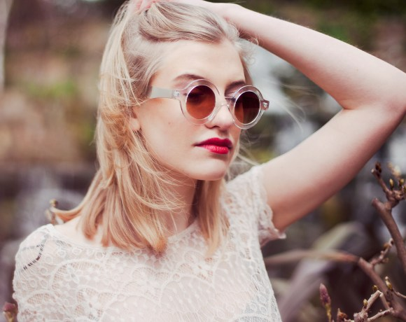 blond girl with sunglasses on and a white lace top in a park