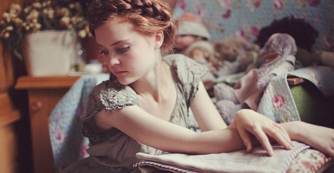 redhead girl with a heidi braid looking like a doll in front some flowers and retro decor