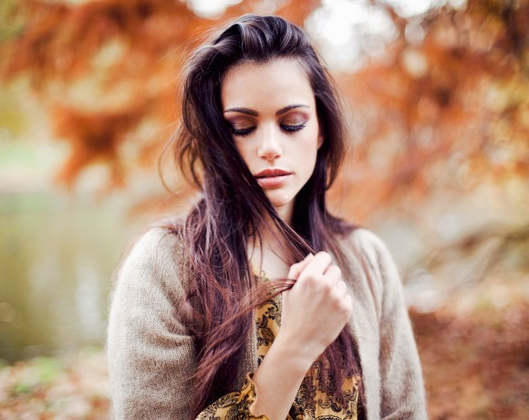 model with dark hair in front of autumnal tree
