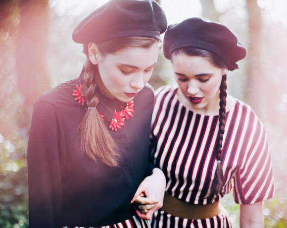 two girls in berets and braids in a forest