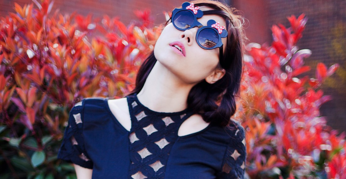 Girl with dark hair and sunglasses on in front of a red bush
