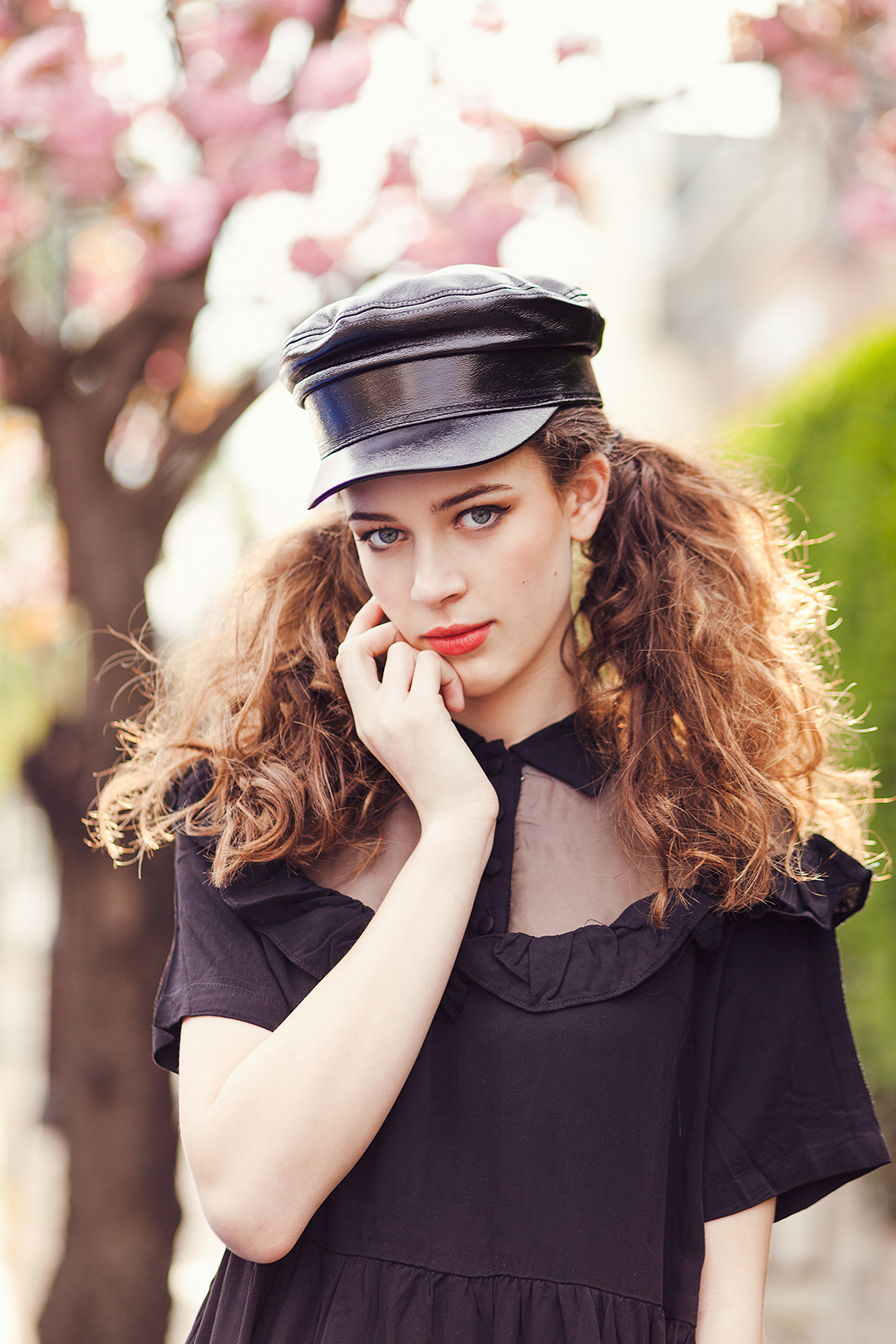 model with brown curly hair with red lips and black dress and hat in front of cherry blossom tree. Angel @ PRM agency model test by Ailera Stone