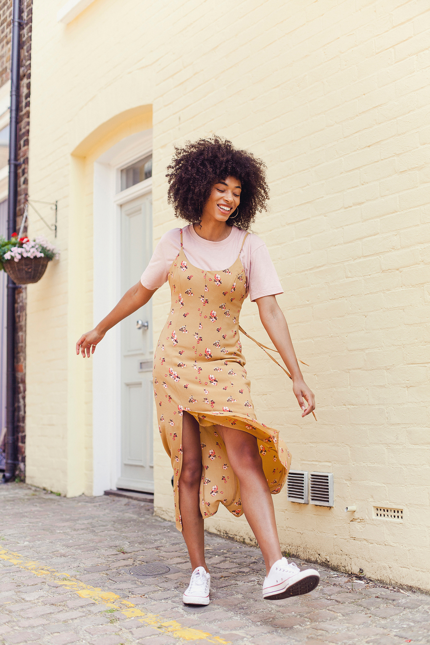 Portrait of fashion blogger Lesley from Asos in Notting Hill by Ailera Stone. Twirling in a floral yellow dress in front of a yellow wall