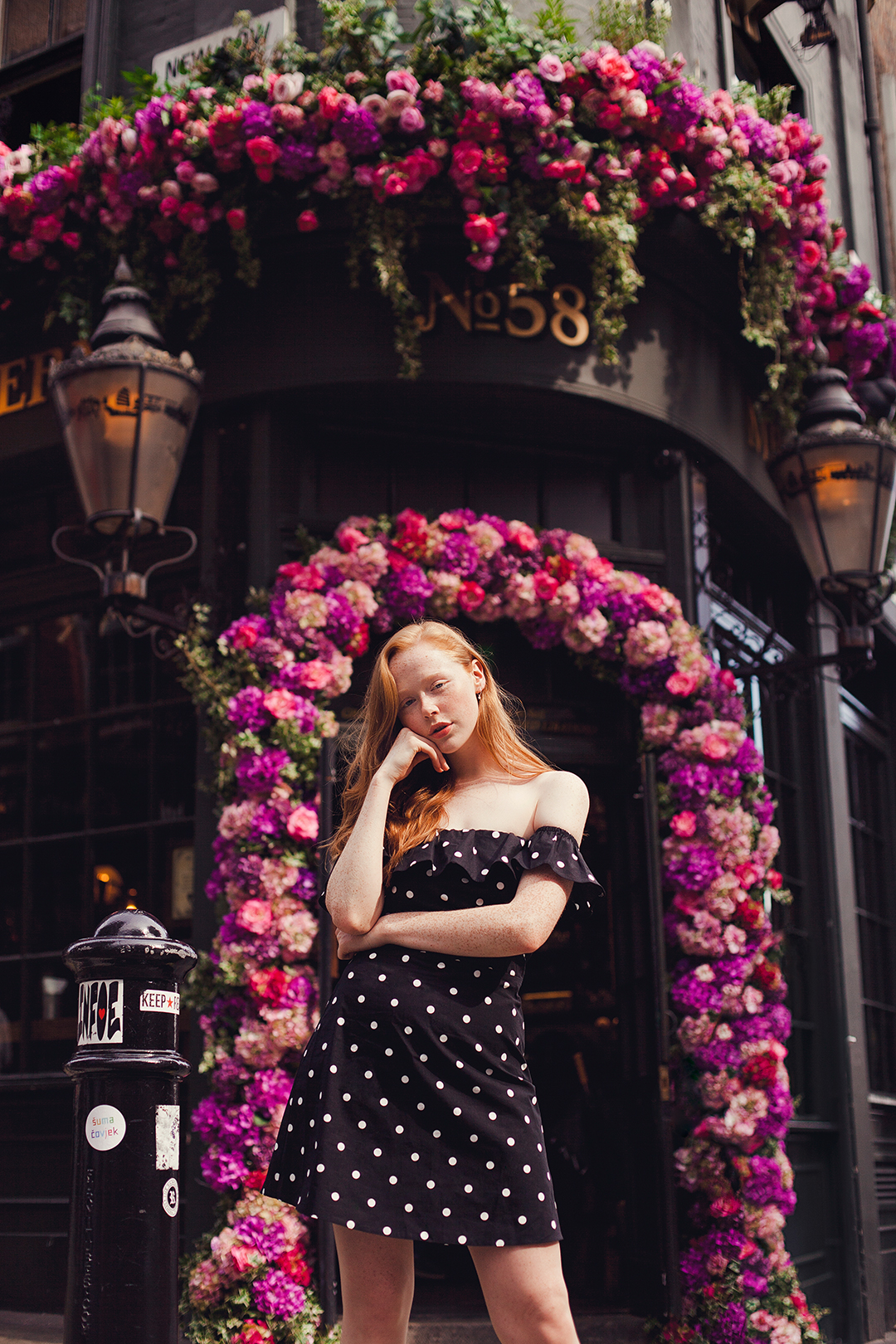 Redhead fashion blogger Holly Rebecca White in front of flower pub by Ailera Stone