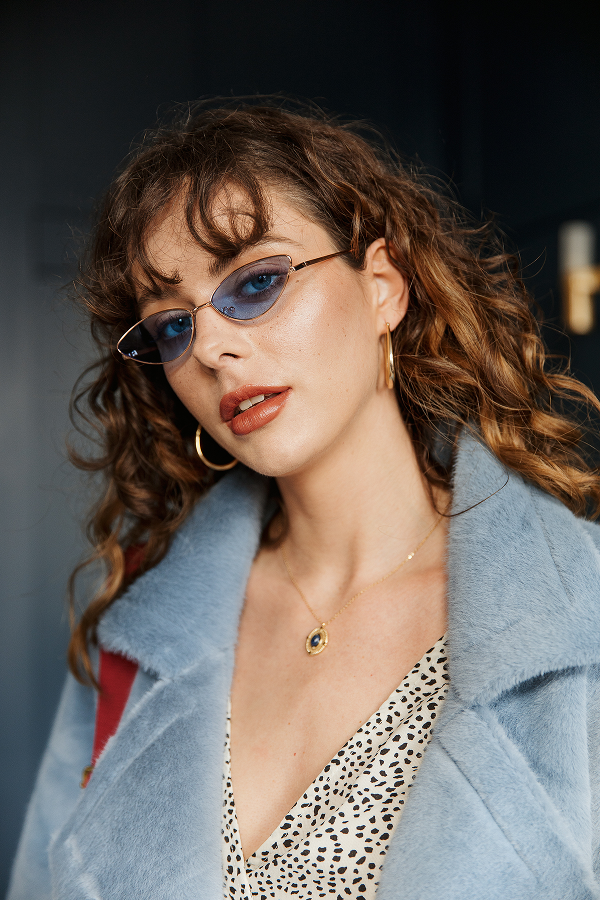 Sugar + Style fashion lookbook and e-com AW 2019. Funky portrait of model Alexandra in blue tinted sunglasses. Shot by London based fashion photographer Ailera Stone