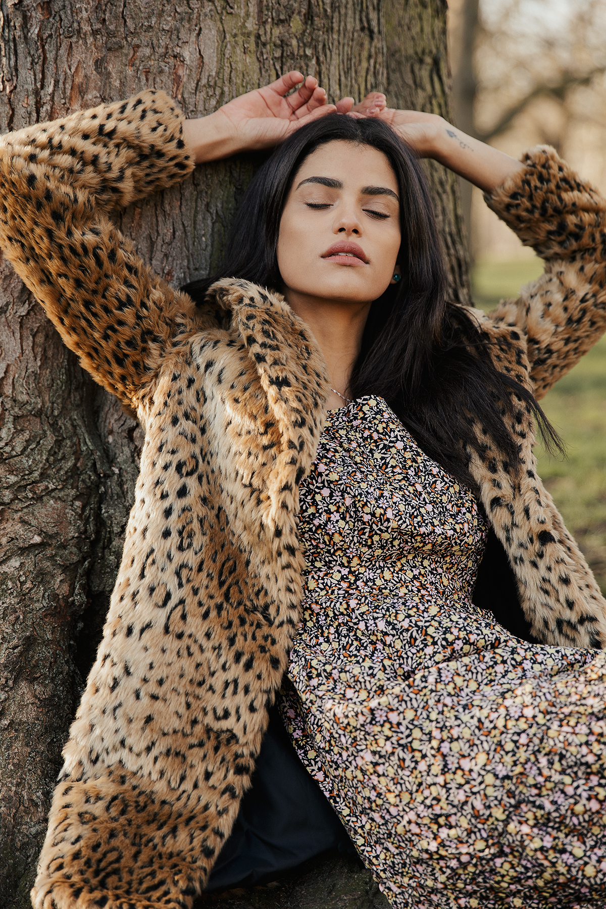 model with black hair sitting against her tree with her hands up and eyes closed