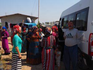 distributing goods refugee camp man posing one arm