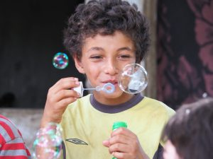 refugee kid blowing bubbles