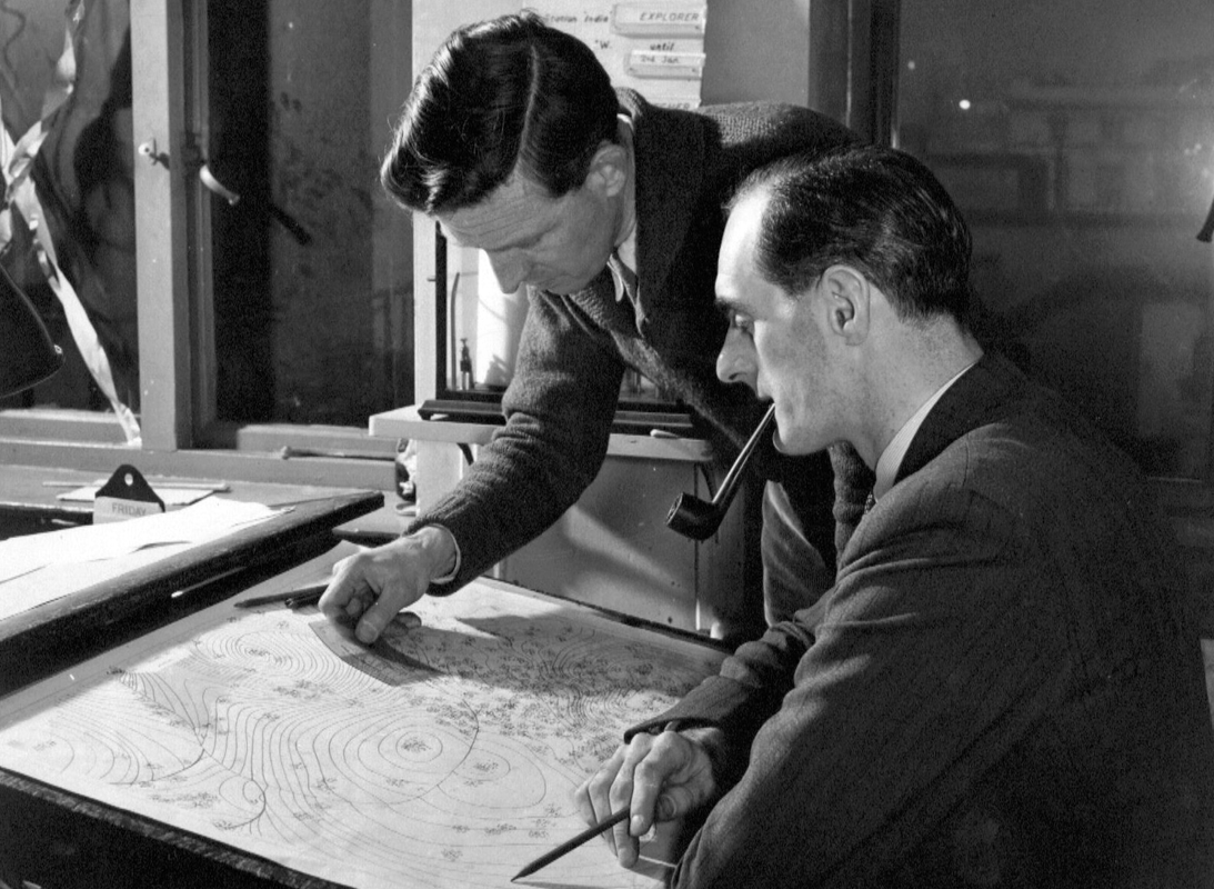 PICTURED: original BBC TV weathermen Tom Clifton (left) and George Cowling (right) looking over maps (1954).