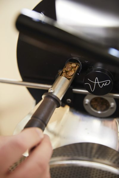Trier pulling out beans from the roasting drum to monitor progress.