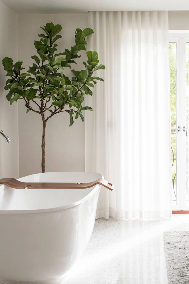 From the ethereal sheer curtains to the shiny white floors and porcelain tub, we love every last detail in this bathroom