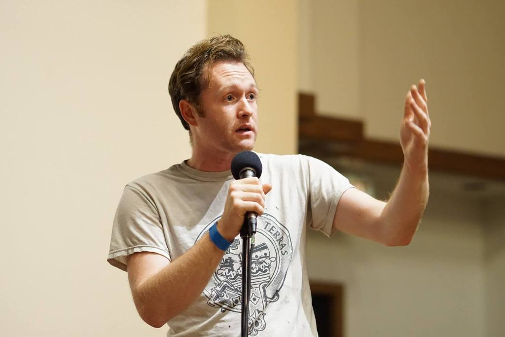 Dan MacDonald holding a microphone and gesturing with his left hand