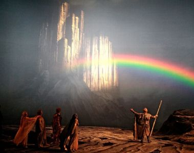 """A godlike figure stands holding a scepter on a golden stretch of earth, observed by a group of people. Image taken from an advertisement for Levine's interpretation of Wagner's """"Ring Cycle"""""""