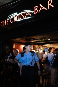 A group of polices were checking people's identity cards in The China Bar, a bar in Lan Kwai Fong at a Saturday midnight.