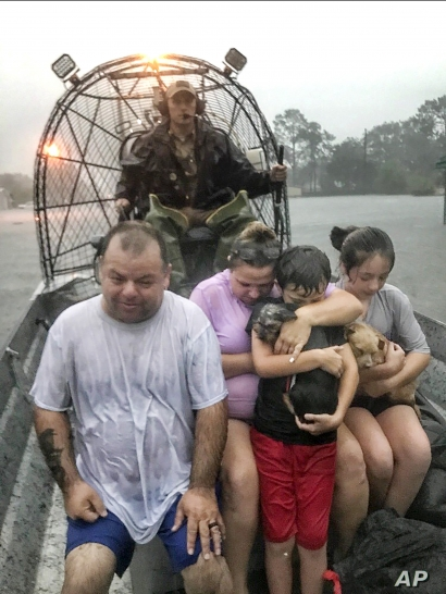 FILE - In this photo provided by the Texas Parks & Wildlife Department, a family is rescued via fan boat by a member of the department from the floodwaters of Tropical Depression Imelda near Beaumont, Texas, Sept. 19, 2019.
