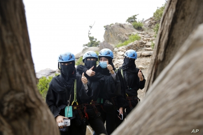 Saudi tourists wear helmets and keep their faces and hair covered according to local custom, as they pose for a photo before zip lining between cliffs, during the al-Soudah festival in Abha, southwest Saudi Arabia, Aug. 23, 2019.