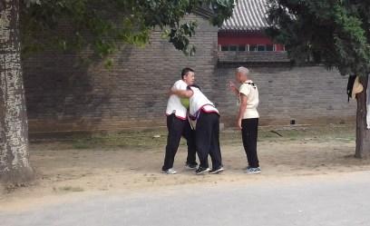 Instrução do mestre Li para dois alunos sobre o uso de técnicas para luta.