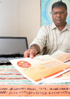 "Bhupi Maru with ""Joy of Giving Week"" posters"
